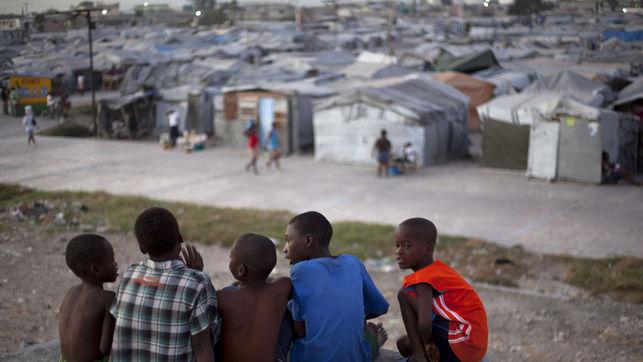 Un grupo de niños se sientane en la terraza de una casa dañada por el terremoto de 2010, frente al campamento de Jean Marie Vincent donde todavía residen, en Puerto Príncipe, Haití./ Fotografía: Nalio Chery (AP)